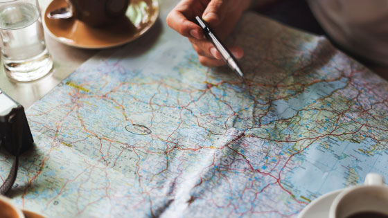 A person holding a pen over a map planning to travel.