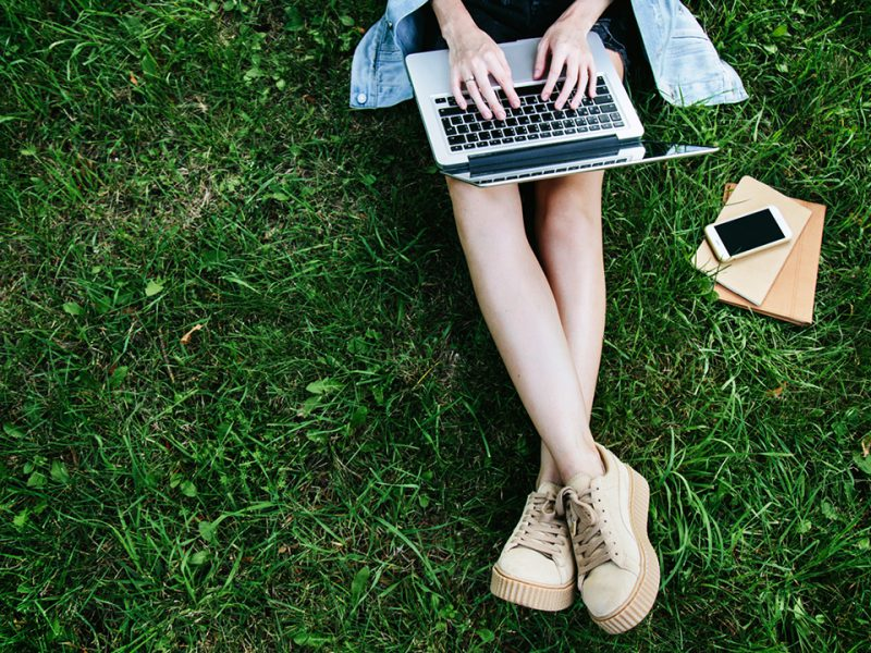 Young girl sitting in grass and typing on her laptop.