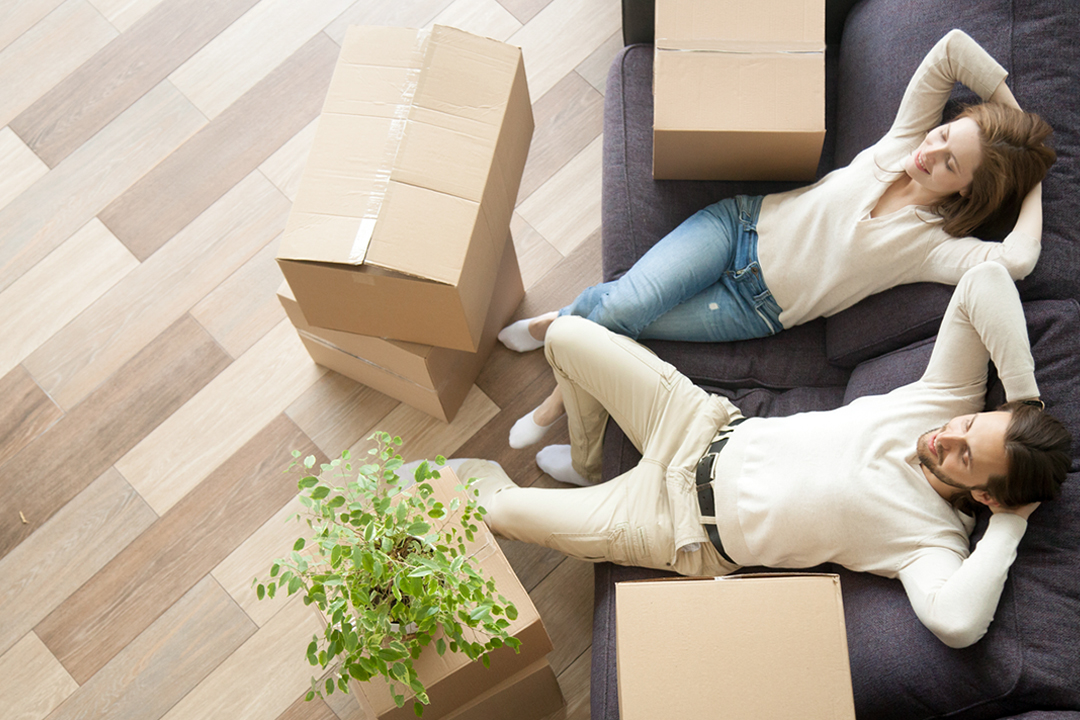 Man and woman relaxing on couch, surrounded by packing boxes.
