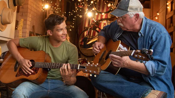 Grandson and grandpa playing their guitars
