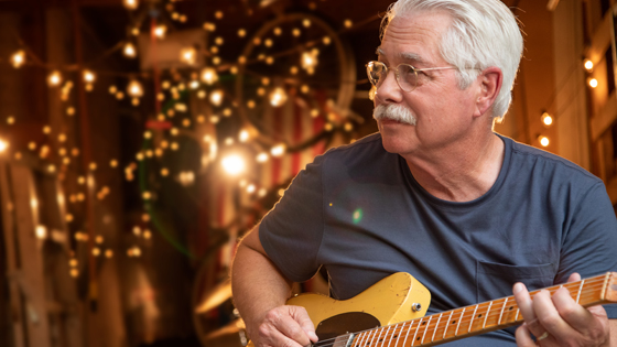 Close up of a grandpa playing his guitar and string lights in the background