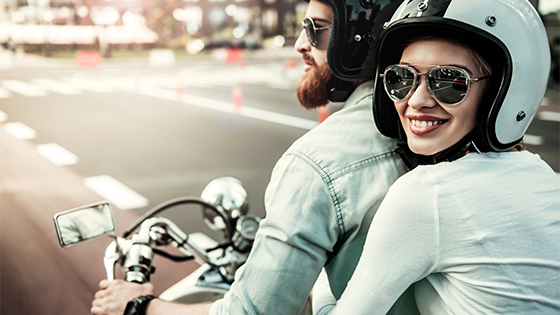 A close up of a women holding onto a man on a motorcycle