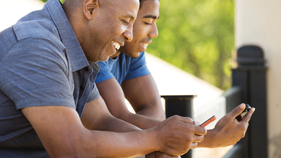 Dad and son looking at there mobile devices