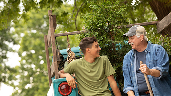 Teen and older man sitting on truck with trees