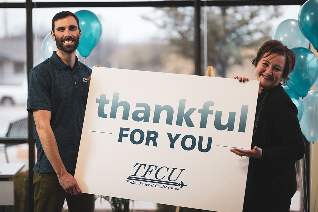 "Two TFCU employees holding a sign that says ""thankful for you"""