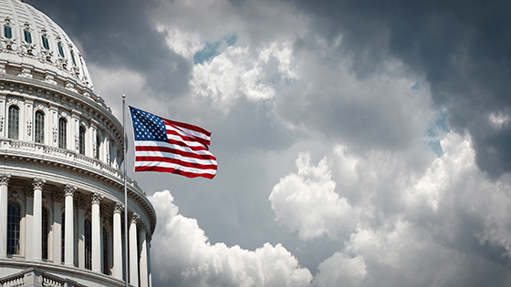 Close up of US Capitol building with waving American flag aganst a cloudy sky.