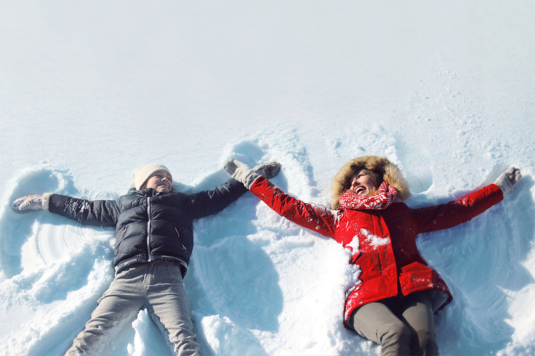 Child in black coat and woman in red coat making snow angels.