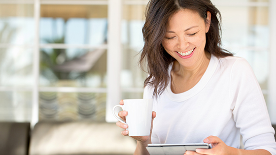 Woman holding mug, looking at her tablet and smiling.