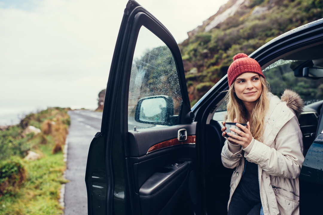 Young woman in red knit hat drinking coffee on a road trip