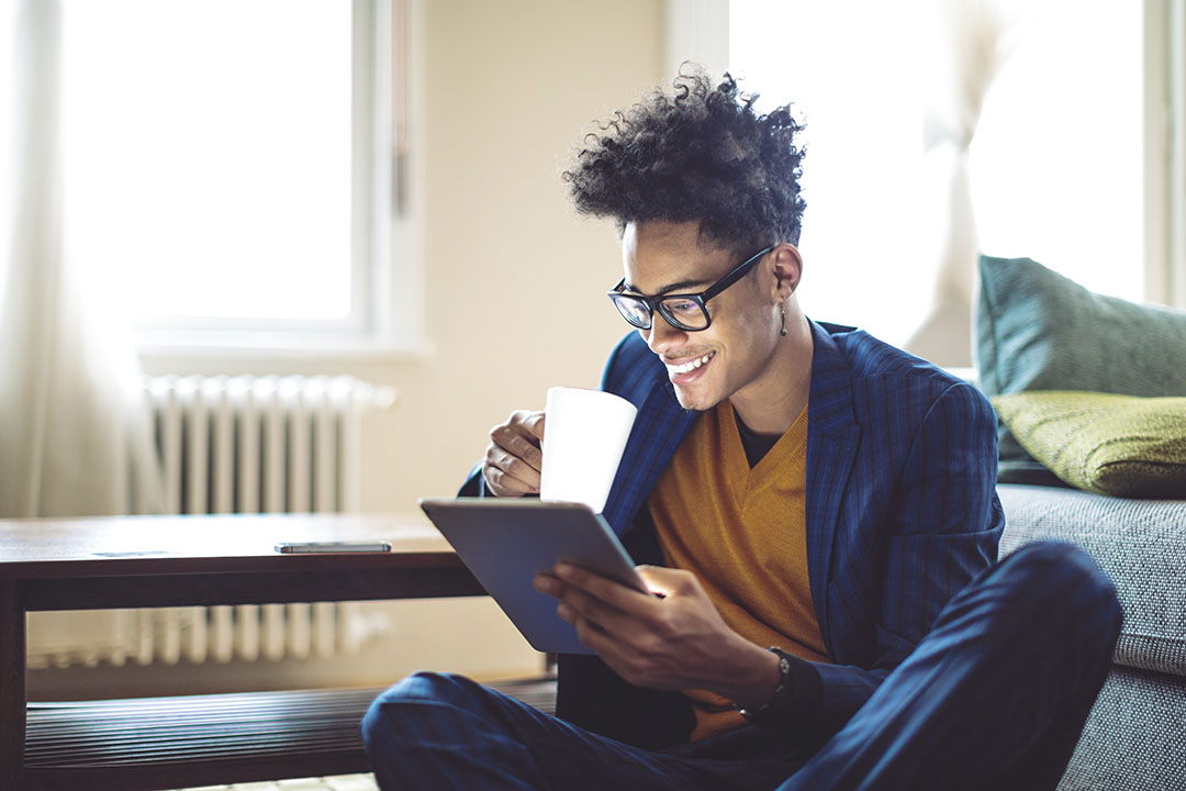 Young man holding mug and reading from tablet.