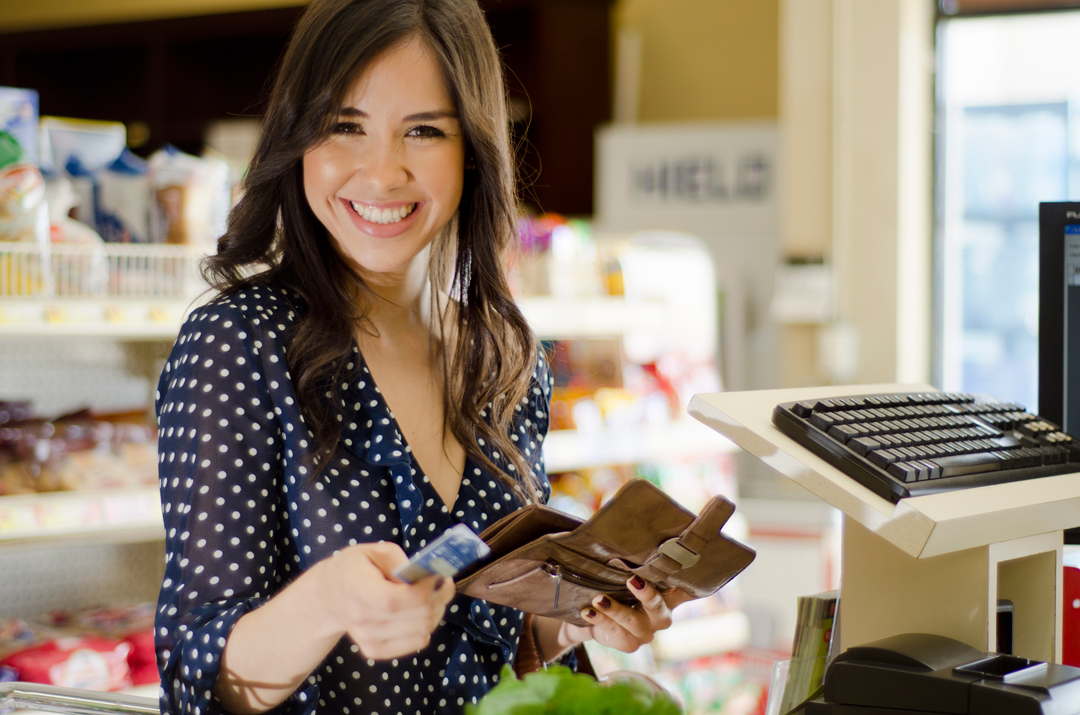 Young woman paying with a credit card in store