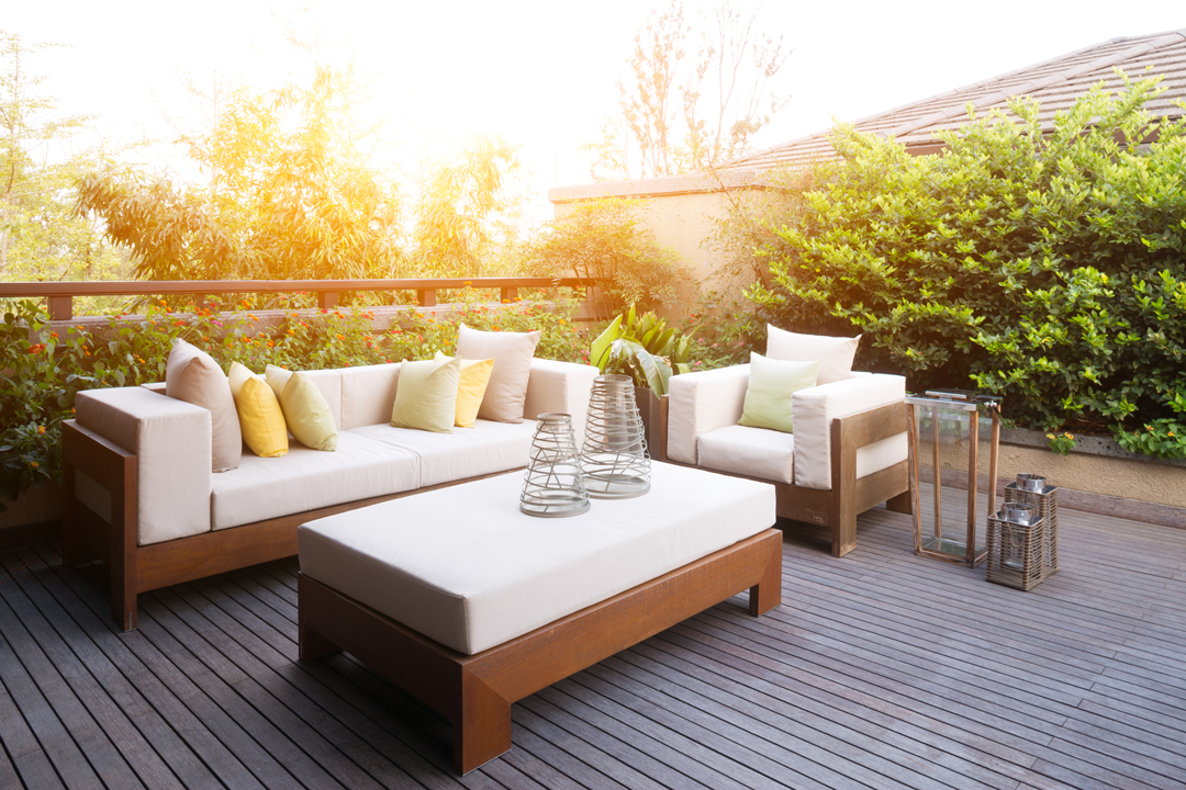 Sunny patio seating area with couch, chair and table