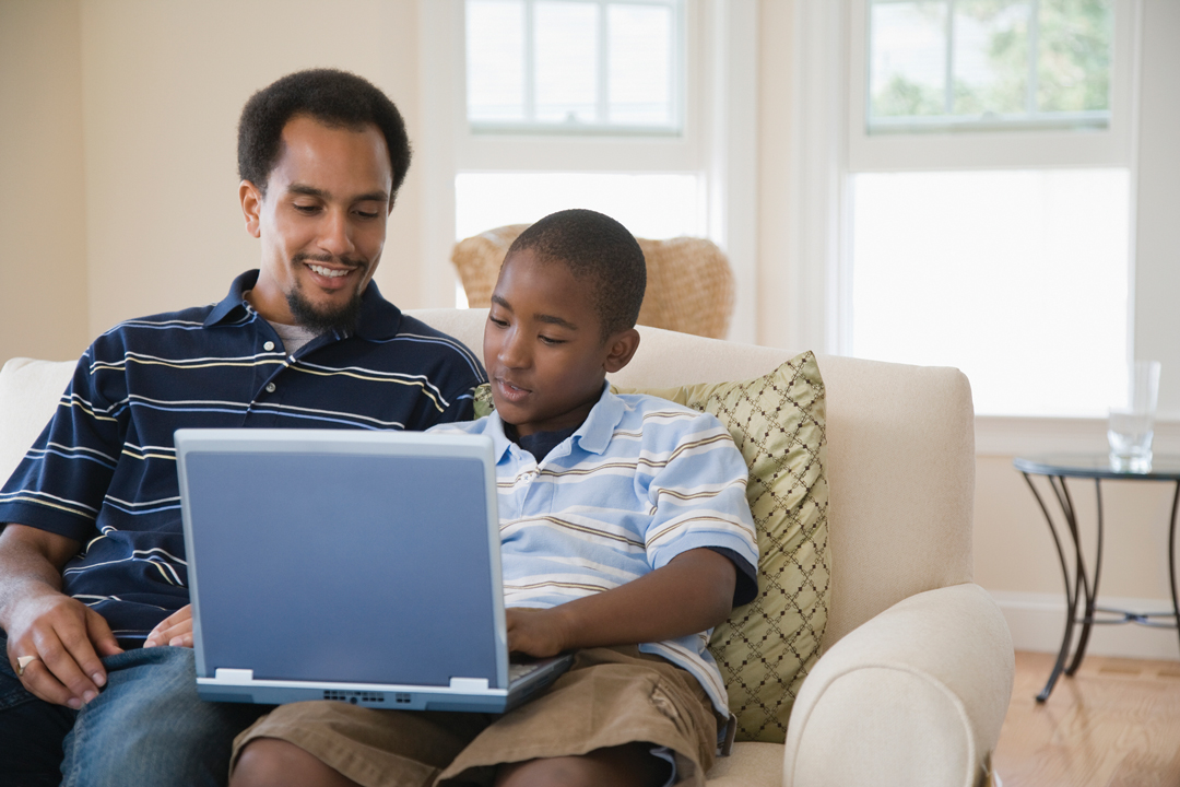 Father and son sitting on couch looking at laptop computer