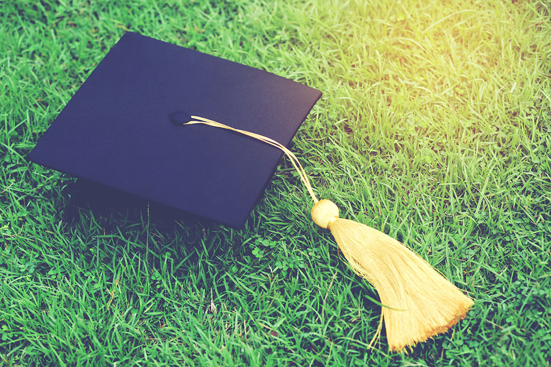 Picture of a navy blue graduation cap with a yellow tassle on the vibrant green grass.