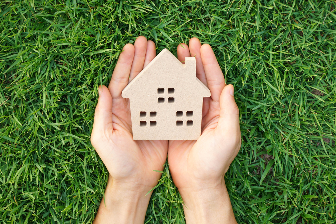 Cupped hands holding a small wood block house over a bed of bright green grass.